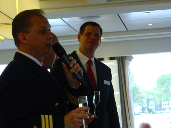Captain Igor Toasts the Passengers, While Gerhardt Looks On